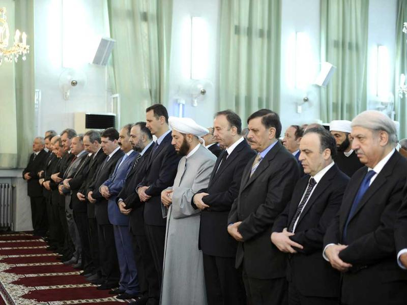 Syria's President Bashar al-Assad (C) takes part in Eid al-Fitr prayers at Anas bin Malek mosque in Damascus (Reuters)