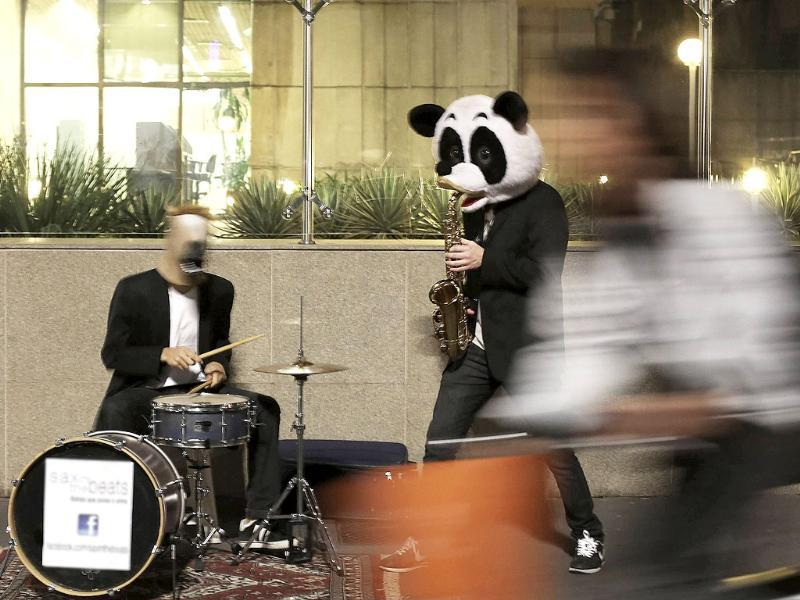 A woman walks past street musicians, wearing horse and panda masks, as they play the saxophone and drums, in Sao Paulo, Brazil. (Reuters Photo)