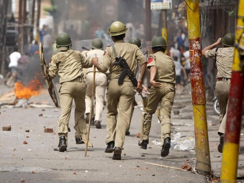 Policemen chase Hindus protesting against the state government after rival communities clashed in Kishtwar, in Jammu. (AP Photo)