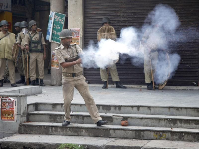 Policemen fire teargas shells towards Hindus protesting against the state government after rival communities clashed in Kishtwar. (AP Photo)