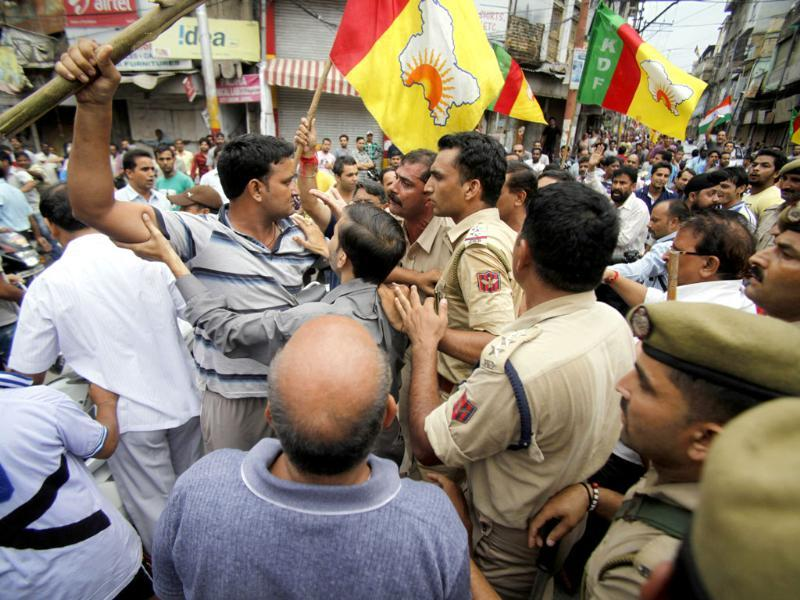 Policemen restrain Hindus protesting against the state government after rival communities clashed in Kishtwar, in Jammu. (AP Photo)