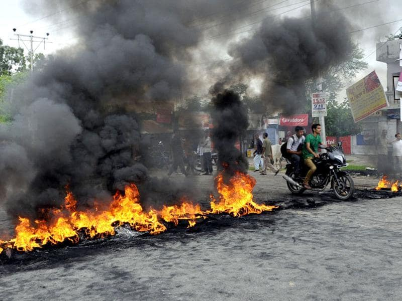 Protestors burn tyres during a protest in Jammu. A town in south Kashmir was under curfew after two people were killed in the disputed region, police said. (Nitin Kanotra/HT Photo)