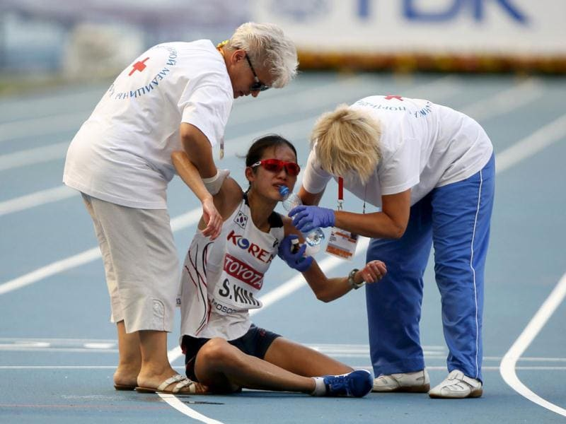 Medics provide help to Seongeun Kim of South Korea after she finished in the women's marathon during the IAAF World Athletics Championships in Moscow. (Reuters Photo)