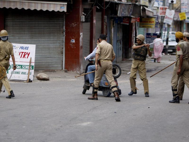 Cops lathi-charge a commuter on a scooter during a curfew in Jammu. (AP Photo)
