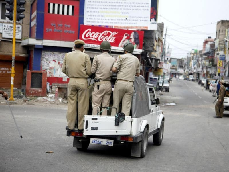 Cops patrol a street during a curfew in Jammu after as communal clashes continued for a third day. (AP Photo)