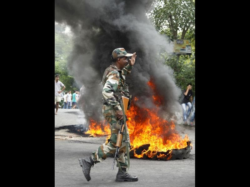 Army soldier walks past tires burned by BJP activists during a protest against the state government in Jammu.(AP Photo)