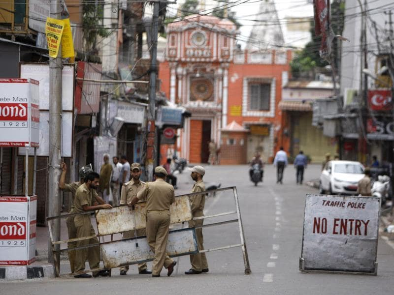 Cops stand near a temple during a curfew in Jammu.(AP Photo)