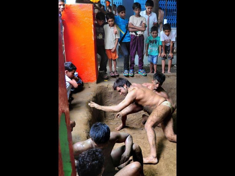 Wrestlers grapple in the pit at the historic Loknath Vyayamsala on the occasion of Nag Panchami, in Allahabad. (AFP Photo)