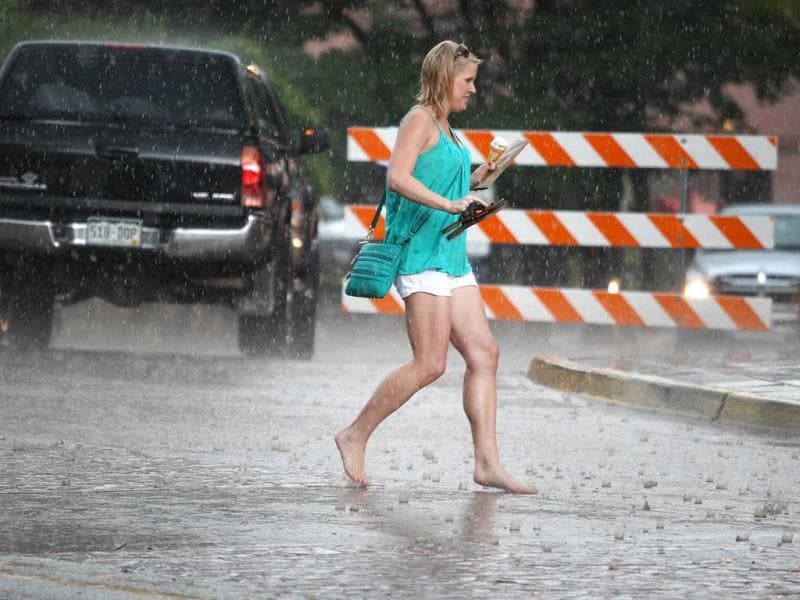 A woman runs for cover in the rain after fire trucks broadcasted a flash flood warning, three days after a deadly flash flood struck the same location, in Manitou Springs, Colorado. (AP Photo)
