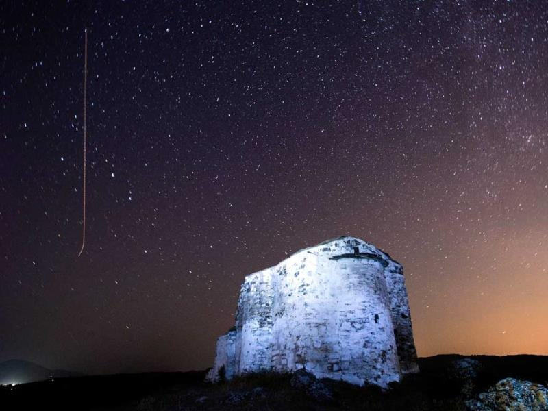A long exposure image showing a Perseids meteor (L) streaking across the night sky over St. Ioan medieval church near the village of Potsurnentsi. (AFP Photo)