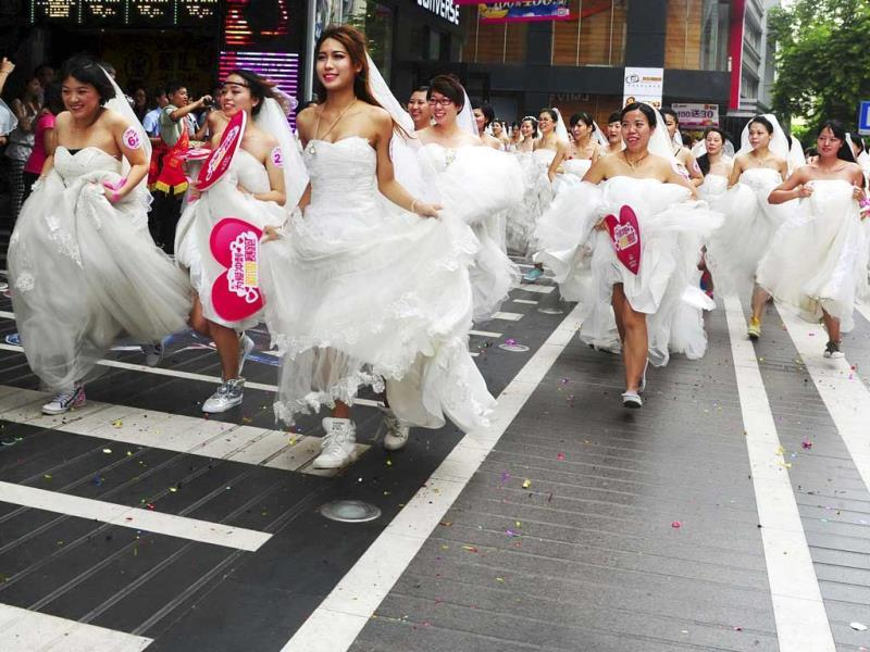 Women in wedding gowns participate in a brides' race event organized by a shopping mall to celebrate the Qixi Festival in Guangzhou, Guangdong province. (Reuters Photo)