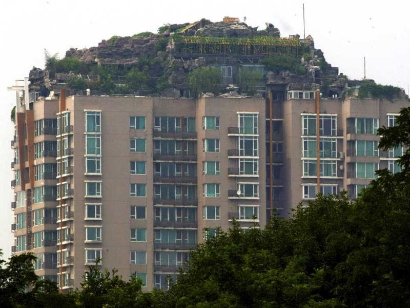 A privately built villa, surrounded by imitation rocks, on the rooftop of a 26-storey residential block in Beijing. (Reuters Photo)