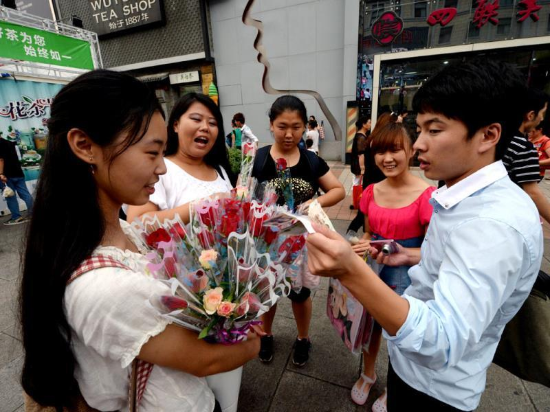 A man buys roses for his girlfriend during the Qixi festival which is also known as the Chinese Valentine's Day in Beijing. The festival dates back over 2600 years and is a popular and auspicious wedding date for Chinese couples. AFP Photo