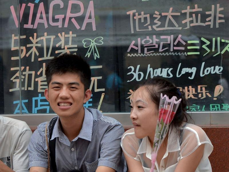 A young girl holds a rose next to her boyfriend as they sit beneath a Viagra sign during the Qixi festival which is also known as the 'Chinese Valentine's Day' in Beijing. AFP