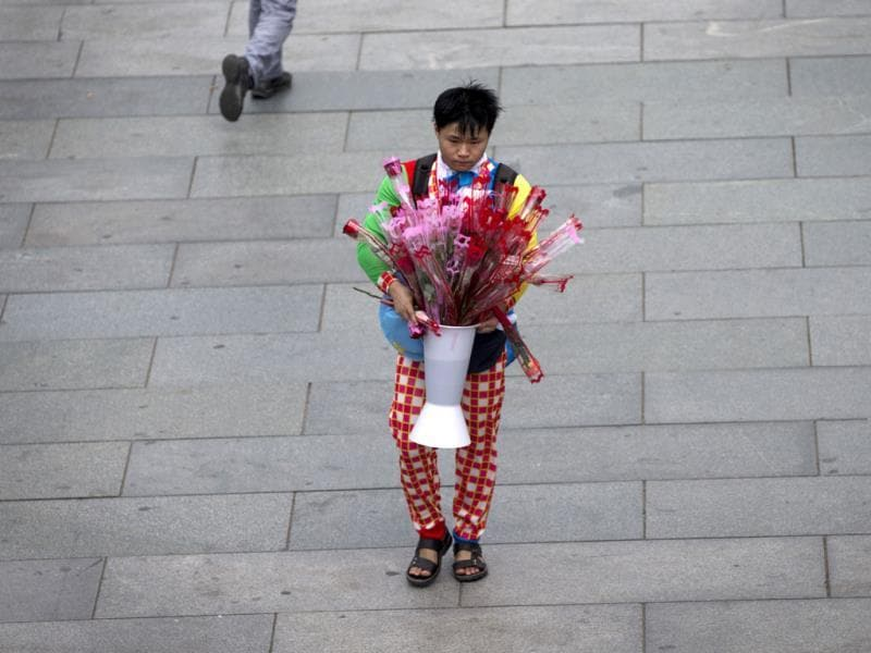 A man dressed in a clown costume sells roses near a shopping district in Beijing on the day of Qixi festival, known as Chinese Valentine's Day. AP