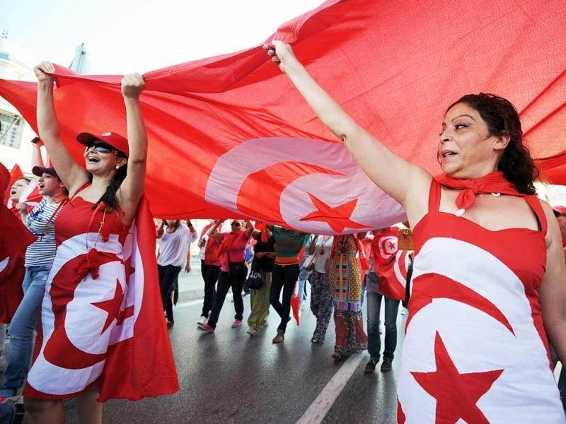 Tunisian demonstrators, bearing the colours of their national flag, shout slogans during a protest against the country's Islamist-led government in front of the Constituent Assembly headquarters in Tunis. (AFP Photo)