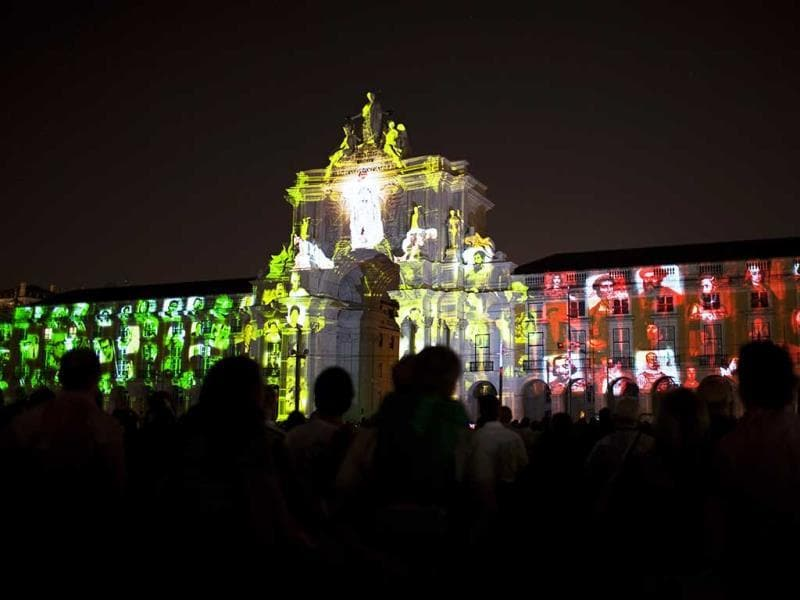 People watch the images of famous Portuguese being projected on the arch of Lisbon's Comercio square. (AP Photo)
