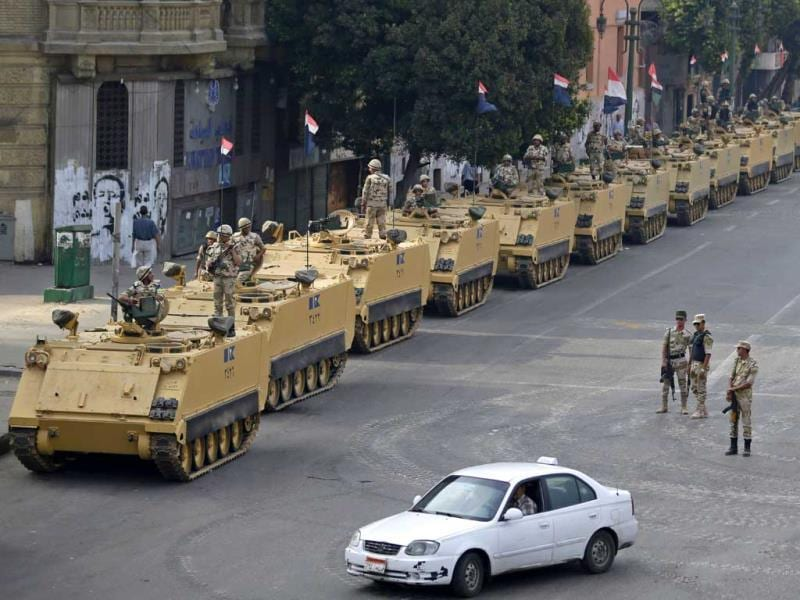 Egyptian army soldiers take their positions on top and next to their armored vehicles while guarding an entrance to Tahrir square, in Cairo, Egypt. (AP Photo)
