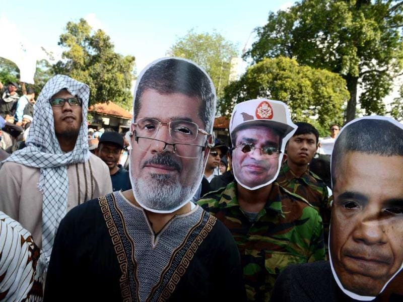 An Indonesian demonstrator wears a mask bearing the portrait of ousted Egyptian Islamist president Mohamed Morsi (C), next to his