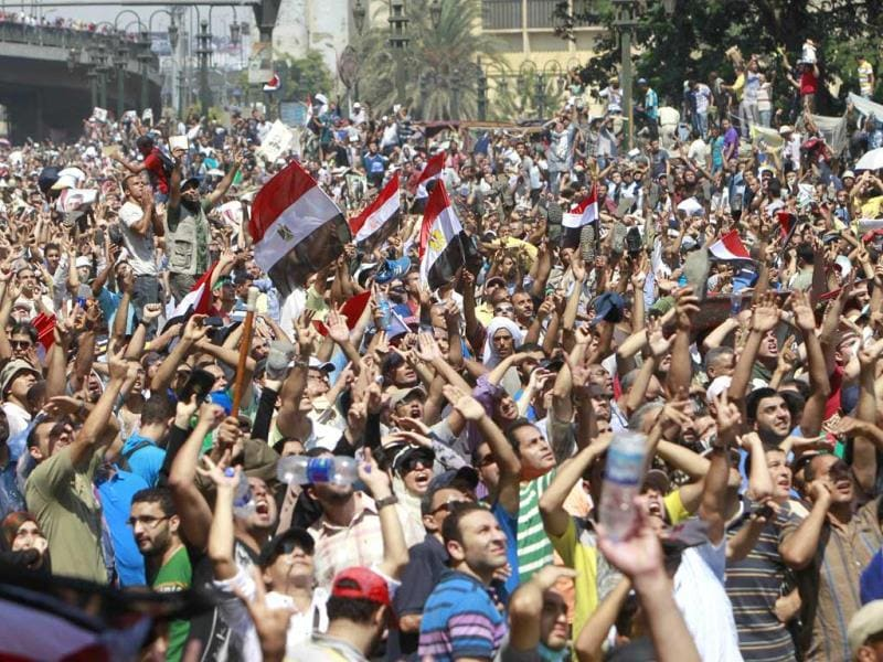 Supporters of deposed Egyptian President Mohamed Mursi shout slogans and wave Egyptian flags during a protest outside Al-Fath Mosque in Ramsis square in Cairo. (AFP Photo)