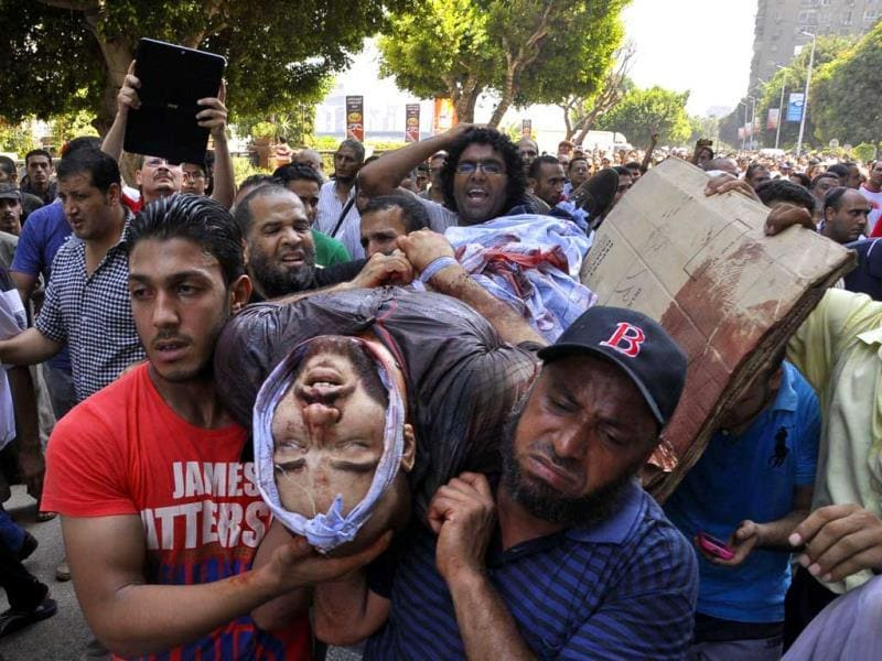 Egyptian Muslim Brotherhood supporters carry the body of a comrade who was shot during clashes with security forces in Giza district on the outskirts of Cairo. (AFP Photo)