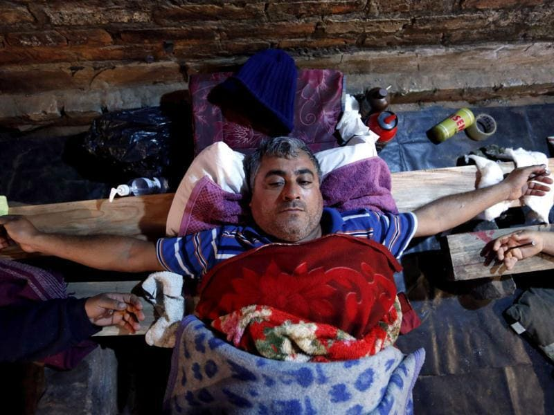 Bus driver Felix Aguero lies with his hands nailed to a wooden cross during a protest in Luque, a town in the outskirts of Asuncion, Paraguay. (AP Photo)