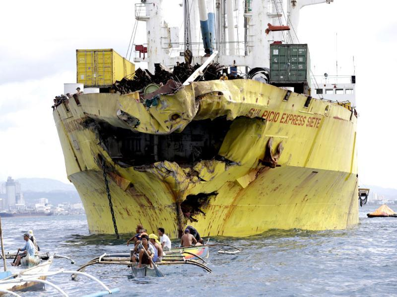 Volunteers search near the damaged cargo ship Sulpicio Express Siete a day after it collided with a passenger ferry off the waters of Talisay city, Cebu province in central Philippines. (AP Photo)