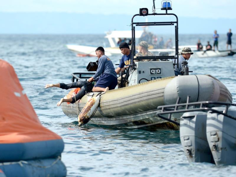 Philippine Navy personnel retrieve a dead body from the sea believed to be one of the passengers from the sunken ferry St. Thomas Aquinas. (AFP Photo)