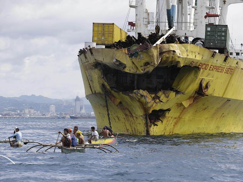 Volunteers search near the bow-damaged cargo ship Sulpicio Express Siete, a day after it sank near Cebu province in central Philippines.(AP Photo)