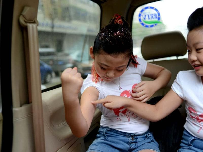 Zhou Zi of Cool (L) showing her muscles in a car before a kid's rock competition in Tianjin. (AFP Photo)