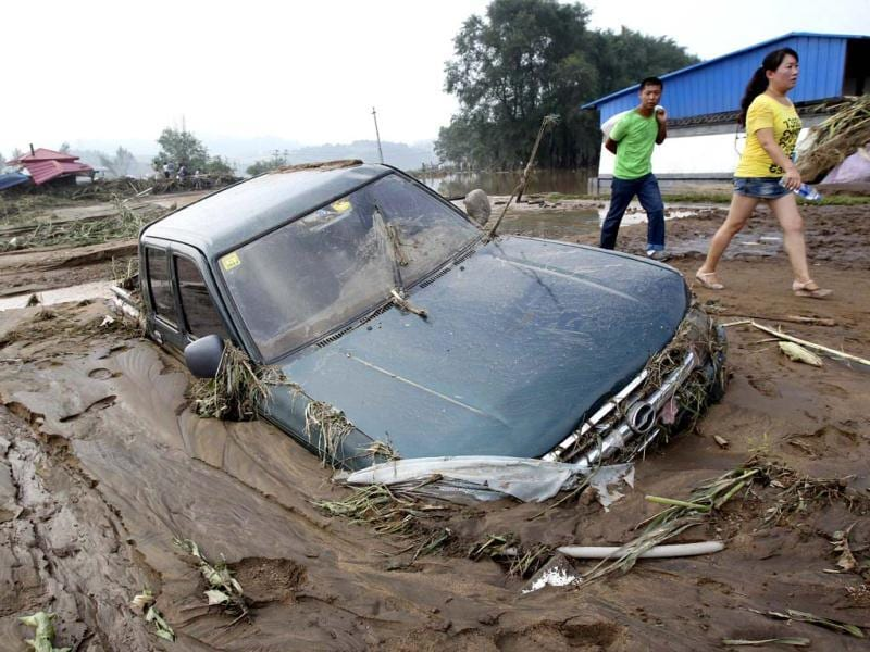 People walk past a car stranded in mud after heavy rainfalls hit Fushun, Liaoning province. (Reuters Photo)