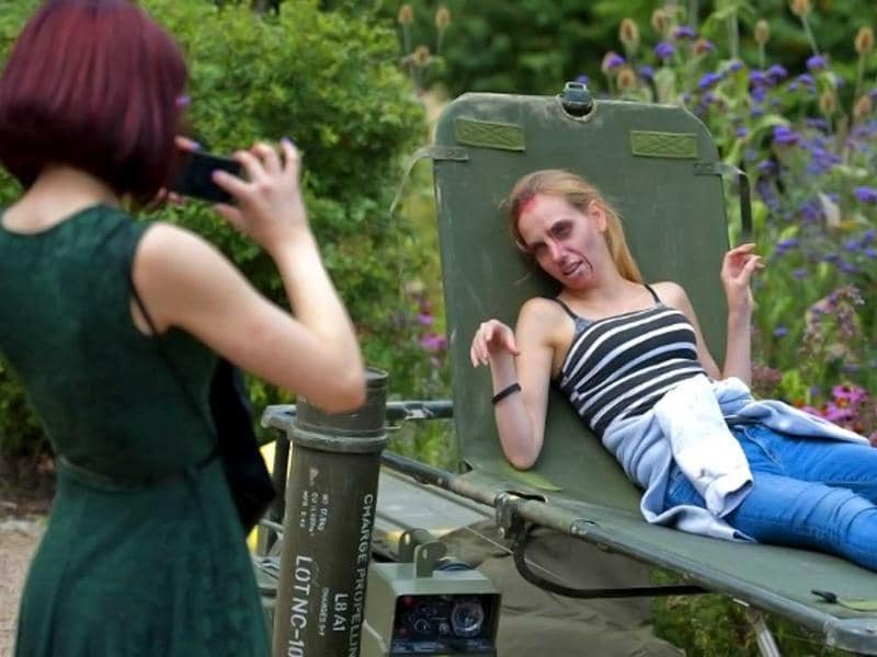 A woman made up to look like a zombie poses for a picture during a Zombie training day in Hyde Park, Central London. AFP photo