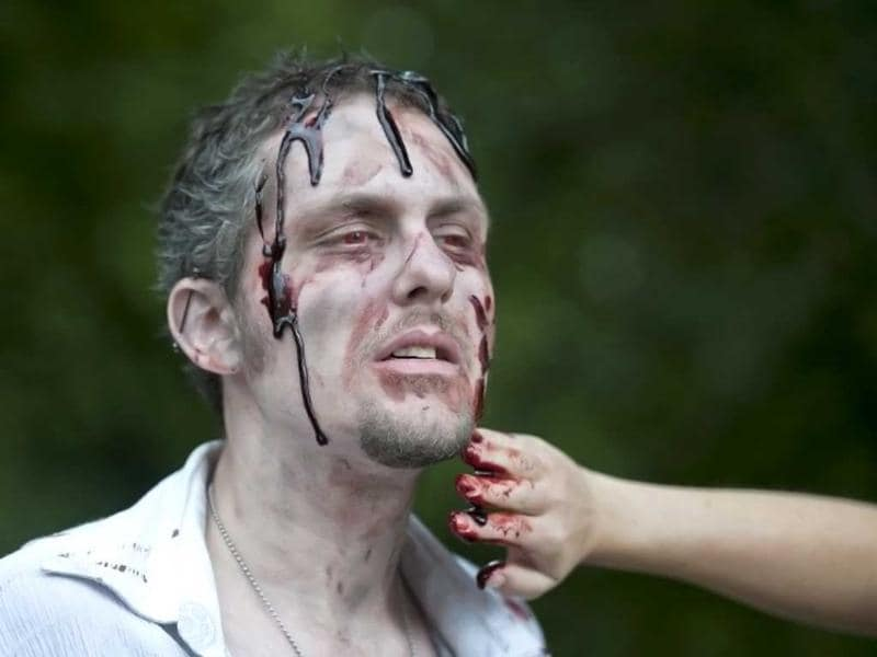 A man gets fake blood applied to look like a zombie during a 'Zombie training day' in Hyde Park, Central London. AFP