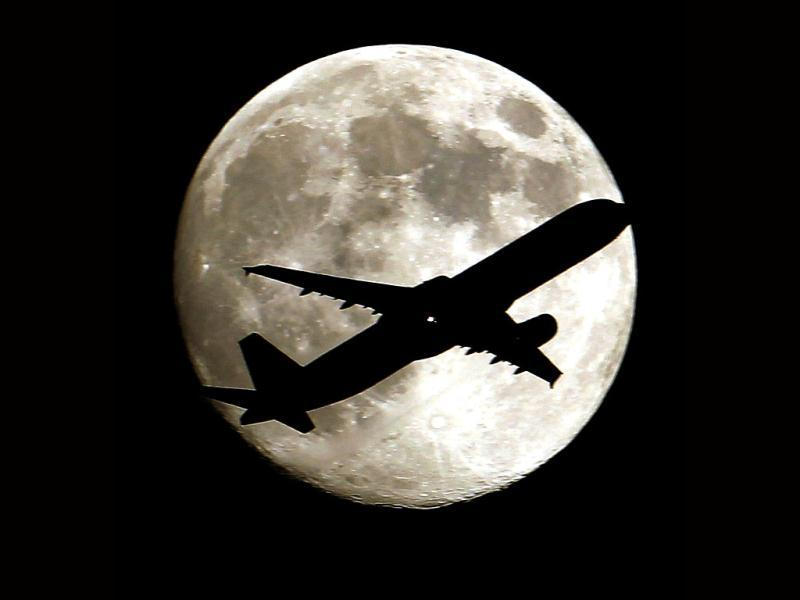 A airlines jet plane approaching Los Angeles International Airport crosses the moon as seen from Palm Park in Whittier, California. (AP Photo)
