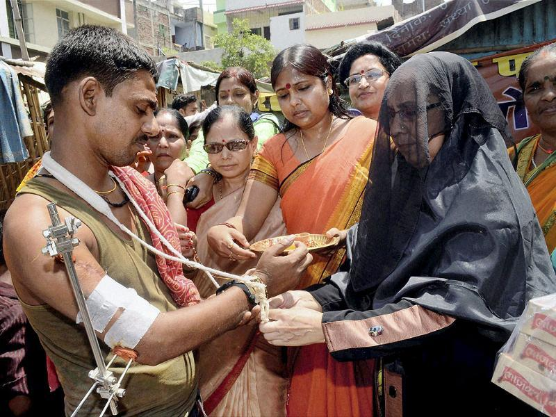 A Muslim woman ties a rakhi on the wrist of a man in a slum area during of Raksha Bandhan celebrations organised by BJP Mahila Morcha in Patna. PTI
