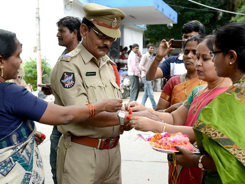 Activists tie rakhis on the wrist of a policeman on the sidelines of a protest against the formation of Telangana state outside the Secretariat in Hyderabad. AFP