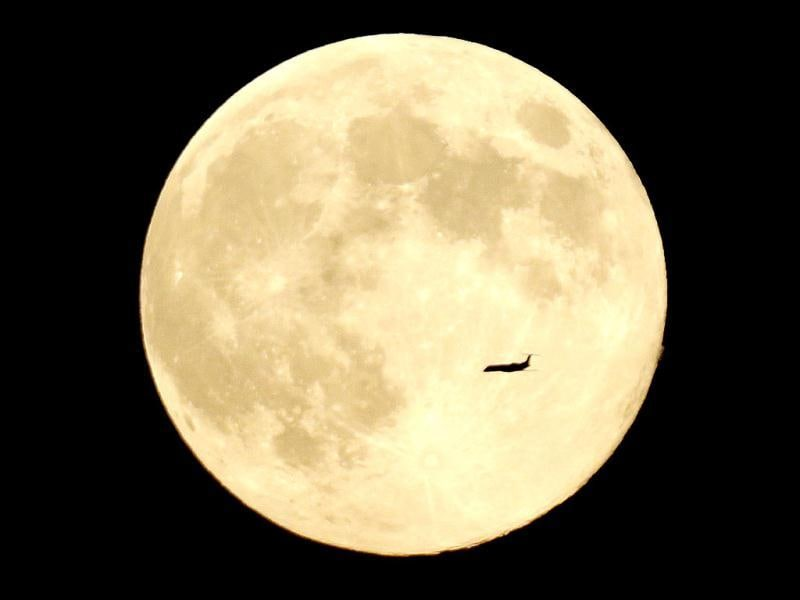 A plane cruises in front of the moon in its full stage under a phenomenon called the blue moon. (AP Photo)