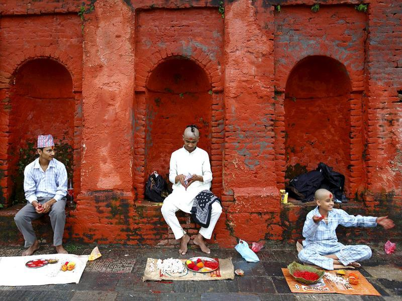 Hindu priests wait for passing devotees to perform rituals during the Janai Purnima, or Sacred Thread, Festival at the premises of Pashupatinath temple in Kathmandu. (Reuters Photo)