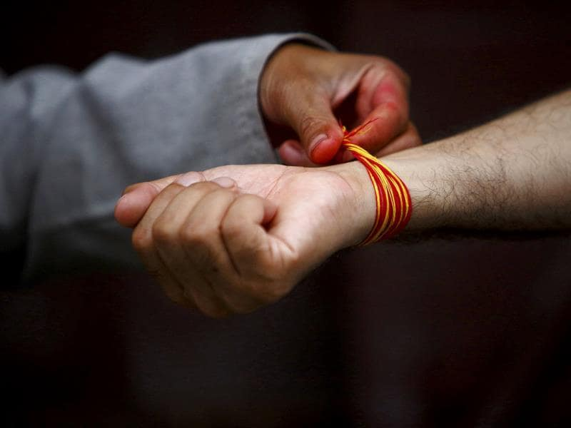 A Hindu priest ties a sacred thread on the hand of a devotee during the Janai Purnima, or Sacred Thread Festival at the premises of Pashupatinath temple in Kathmandu. (Reuters Photo)