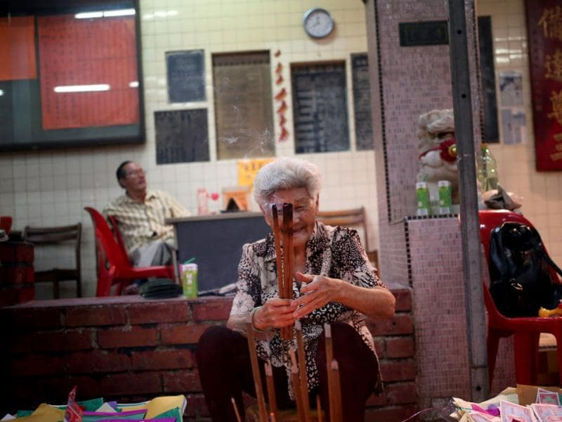 An elderly woman burns incense sticks as offerings during the 'Hungry Ghost Festival' celebrated in Singapore. (AP Photo)