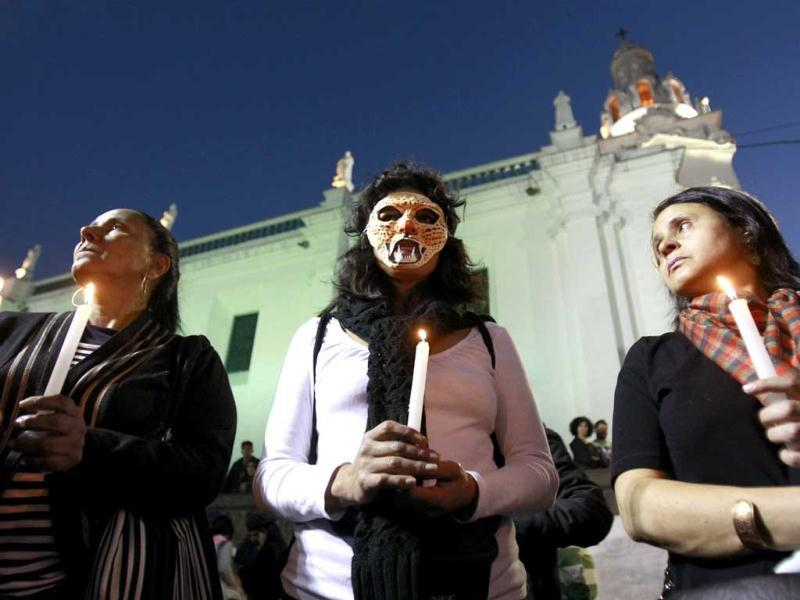 A woman wearing a mask in the likeness of a tigrillo, joins with others in a candlelight vigil, in protest against the government's decision to allow oil drilling in the Amazon reserve, Yasuni National Park, in Quito, Ecuador. (AP Photo)