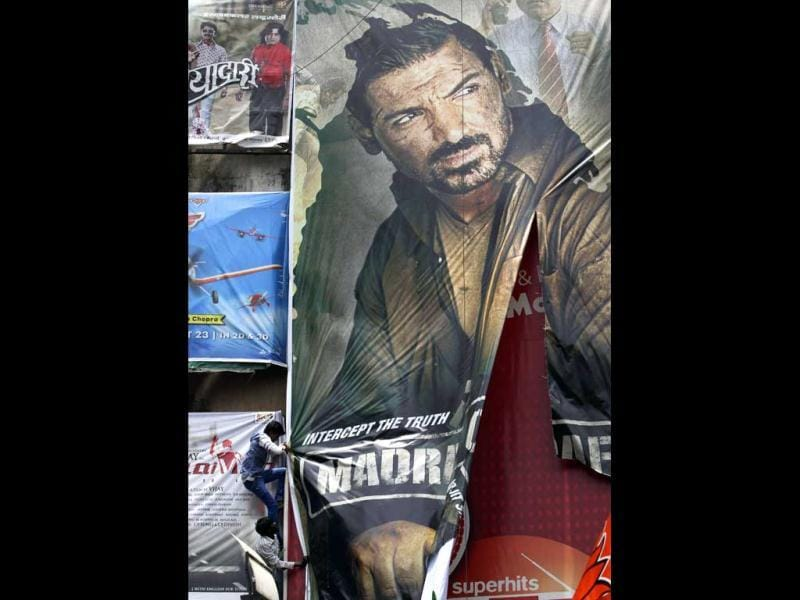 Protestors tear down a poster of Madras Cafe that features actor John Abraham outside a cinema hall in Mumbai. (AP Photo)