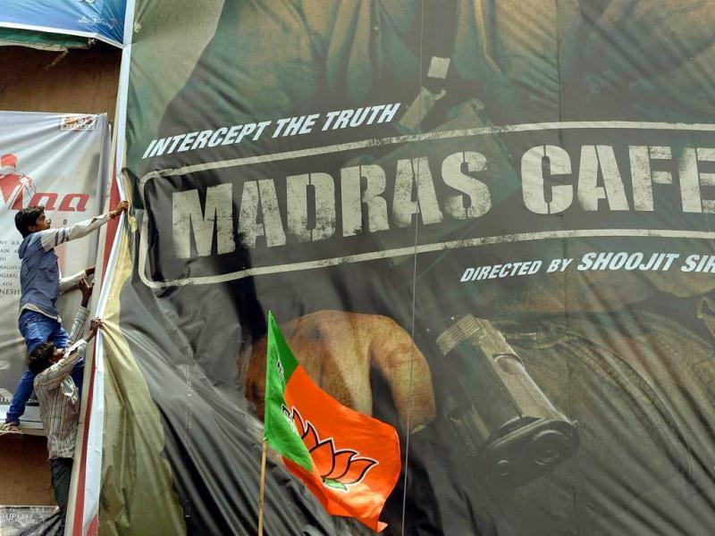 Tamils and Bharatiya Janta Party (BJP) supporters attempt to tear down a poster of John Abraham's Madras Cafe' during a protest against its release at a movie hall in Mumbai. (AFP Photo)