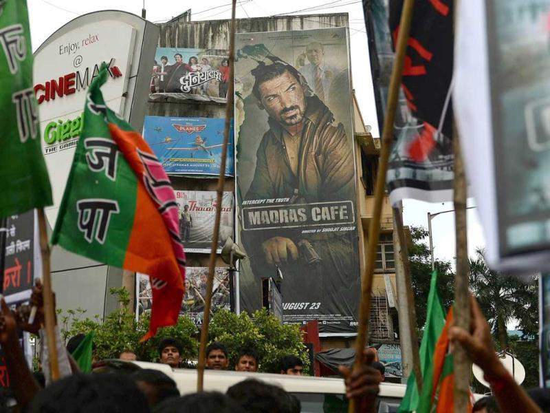 A poster of John Abraham's Madras Cafe is pictured in the background as Indian Tamils and Bharatiya Janta Party (BJP) supporters carry placards and flags as they demonstrate against the release of the movie outside a movie hall in Mumbai on August 22, 2013. (AFP Photo)