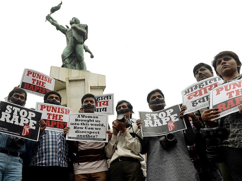 Photojournalists hold placards and cameras as they take part in a protest rally after a female photographer was gangraped in Mumbai. (AFP Photo)