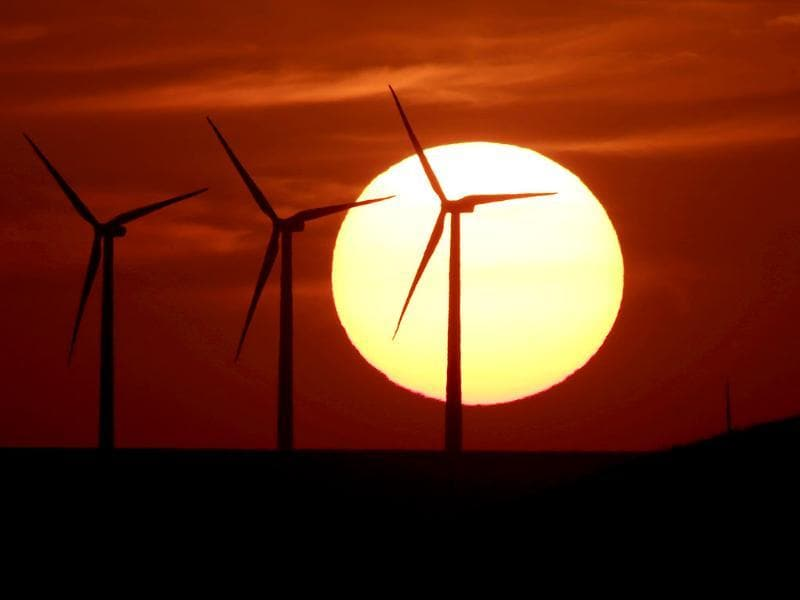 Wind turbines are silhouetted by the setting sun Friday near Beaumont, Kansas. AP photo