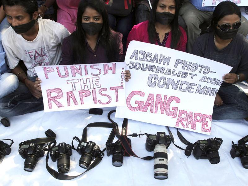 Photojournalists sit with placards during a protest in Gauhati against the gang-rape of a photojournalist in Mumbai that happened on Thursday evening. (AP Photo)