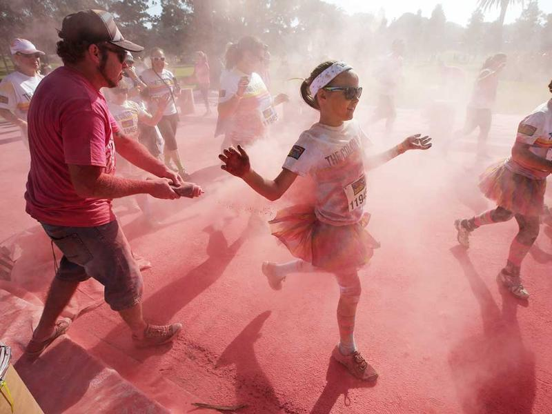 Color powder is squirted onto participants in The Color Run in Sydney, Australia. About 3,000 kilograms of colored corn starch is flung at the 15,000 runners over the 5 km course through Centennial Park. (AP Photo)
