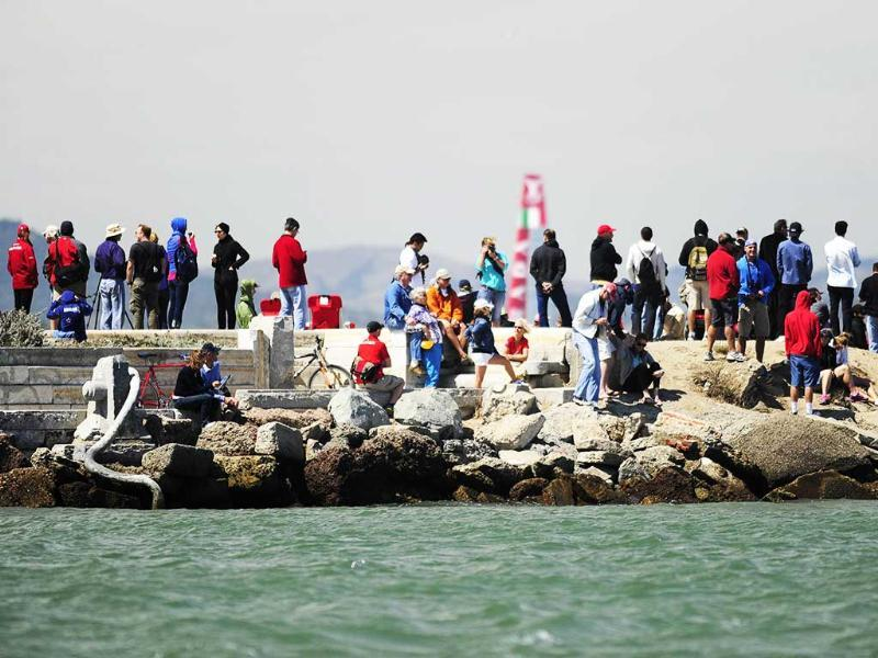 People look on from a breakwater near the San Francisco Yacht Club as Luna Rossa Challenge sails by after completing the seventh race of the Louis Vuitton Cup in San Francisco. AFP photo