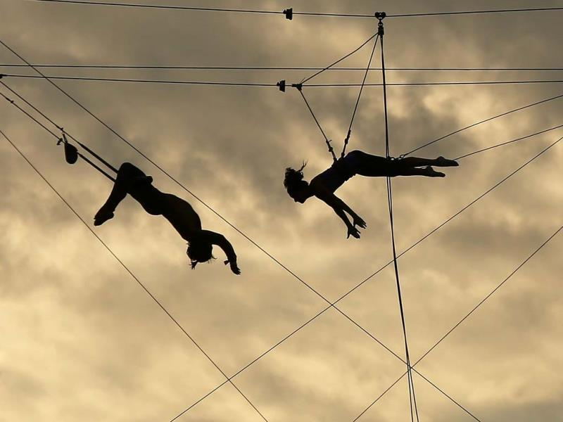 Participants practice on a trapeze at the Trapeze School of New York on the West Side of Manhattan beside the Hudson River on August 26, 2013 in New York City.